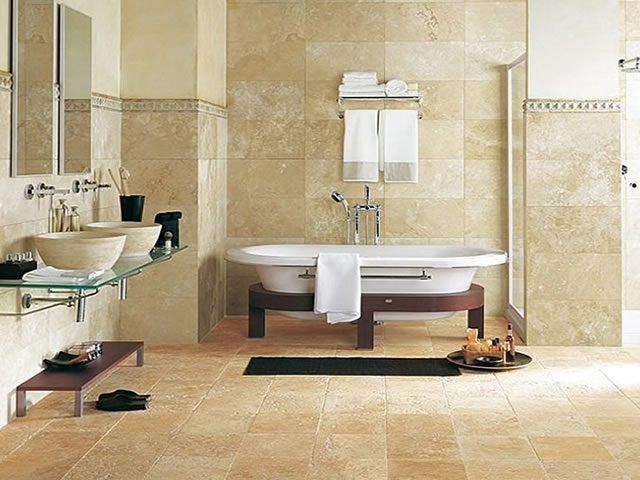 A modern bathroom with all khaki colored tiles, bathtub sits in main focus with raised dual sink and mirror to left side