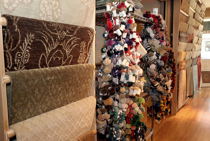 Vertically stacked rugs and hundreds of yarn used for hand-made rugs