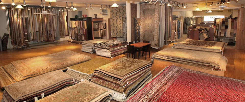 Peerless showroom, with multiple stacks of rugs on floor and rugs hanging along walls