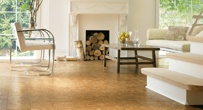 Renewable cork finished floor with chopped wood in background of home and a couch and chairs surrounding