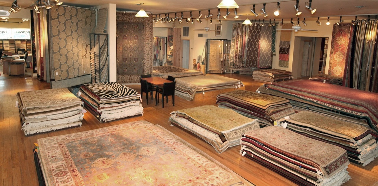 main showroom with multiple stacks of rugs and rugs hanging vertically along wall