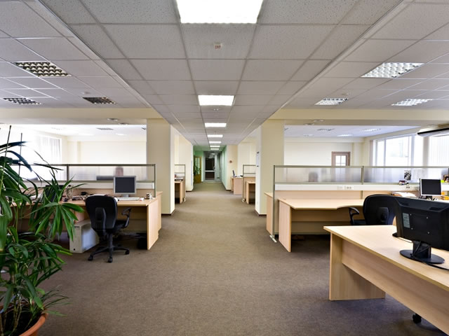 An office hallway with light brown carpeting and desk cubicles on each side